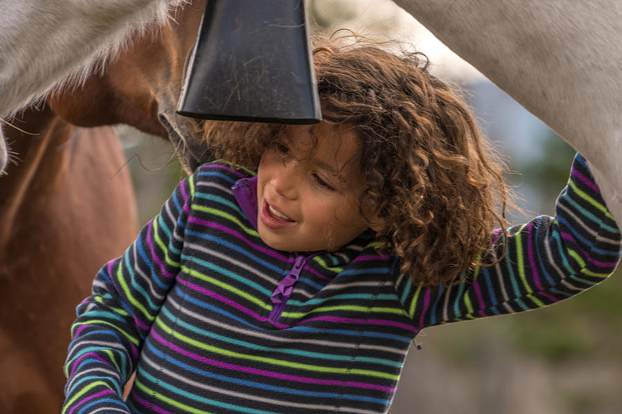 Mixed Race Girl Connects With Horses Below Mountains Photograph by AscentXmedia
