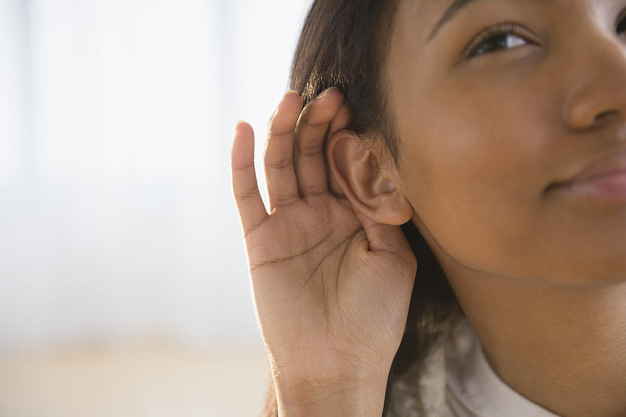 Mixed race woman cupping her ear Photograph by JGI/Jamie Grill