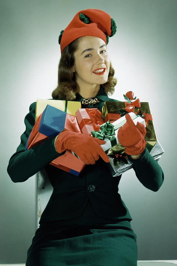 Model Wearing Christmas Hat and Holding Gifts Photograph by John Rawlings