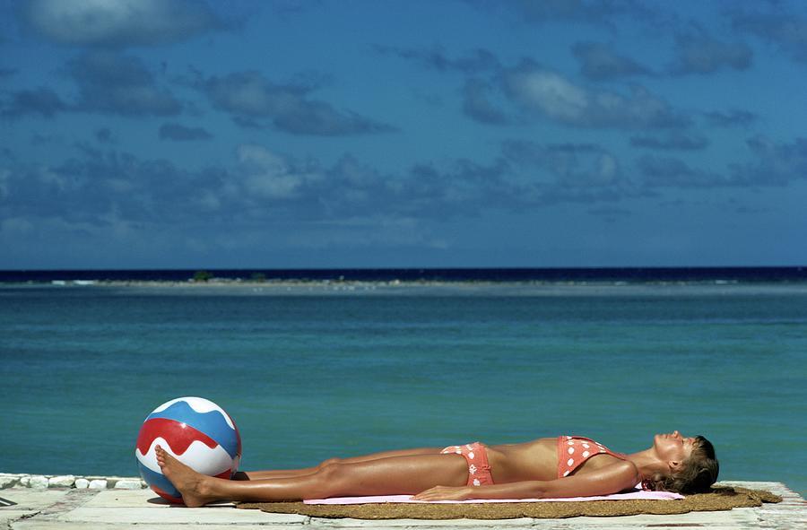 Model Lying on the Beach in a Polka Dot Bikini Photograph by Mike Reinhardt