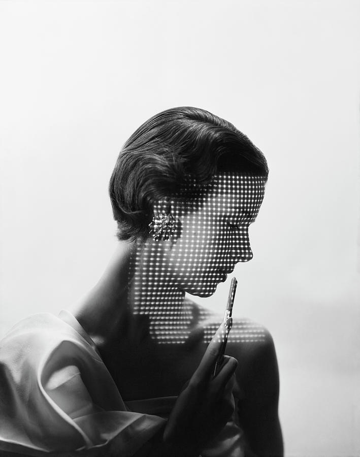 Model With Points Of Lights Reflecting Across Her Face Photograph by Erwin Blumenfeld