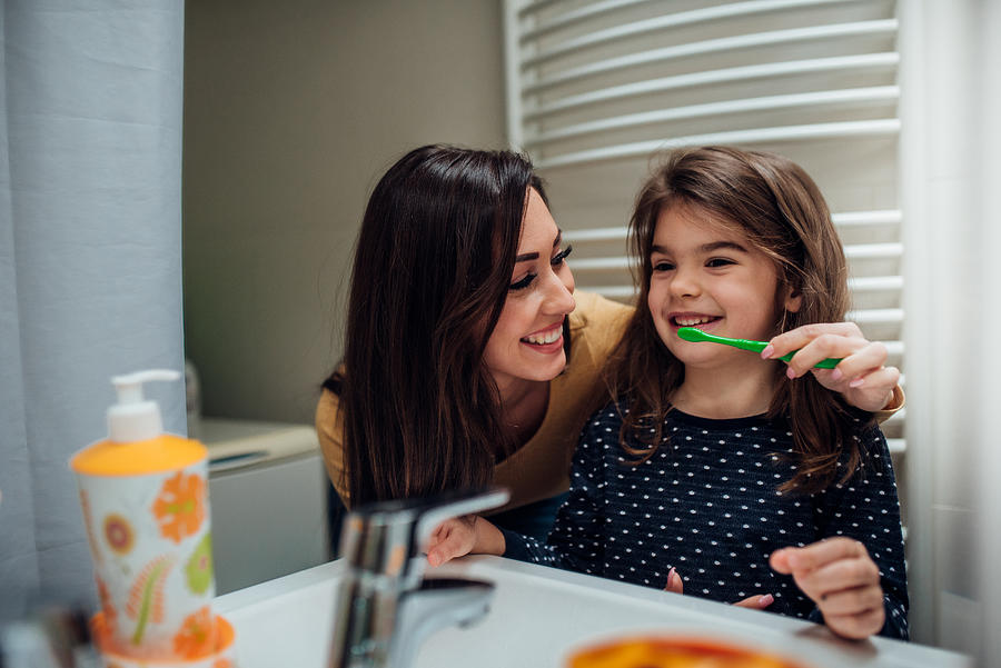 Mother and daughter brushing teeth Photograph by RgStudio