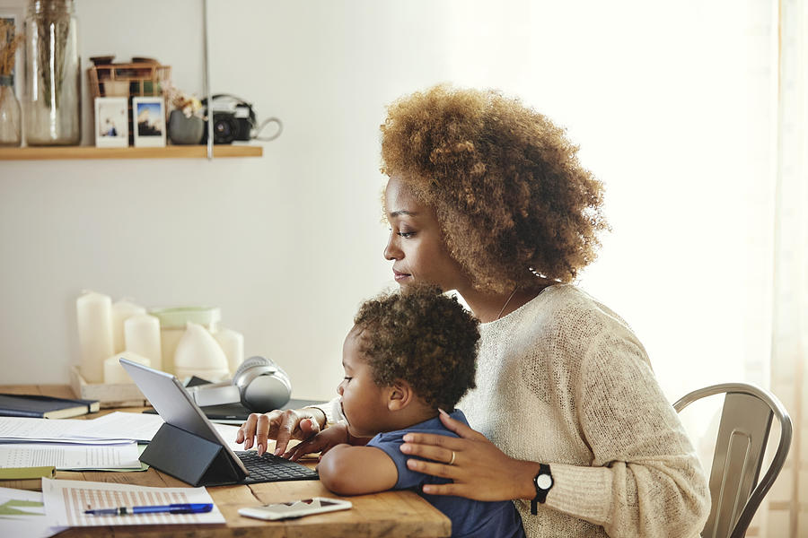 Mother with son working on digital tablet at home Photograph by Morsa Images