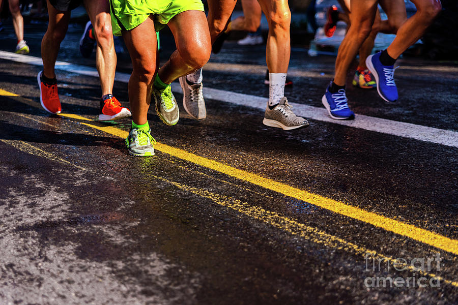 Muscled legs of a group of several runners training running on asphalt by Joaquin Corbalan