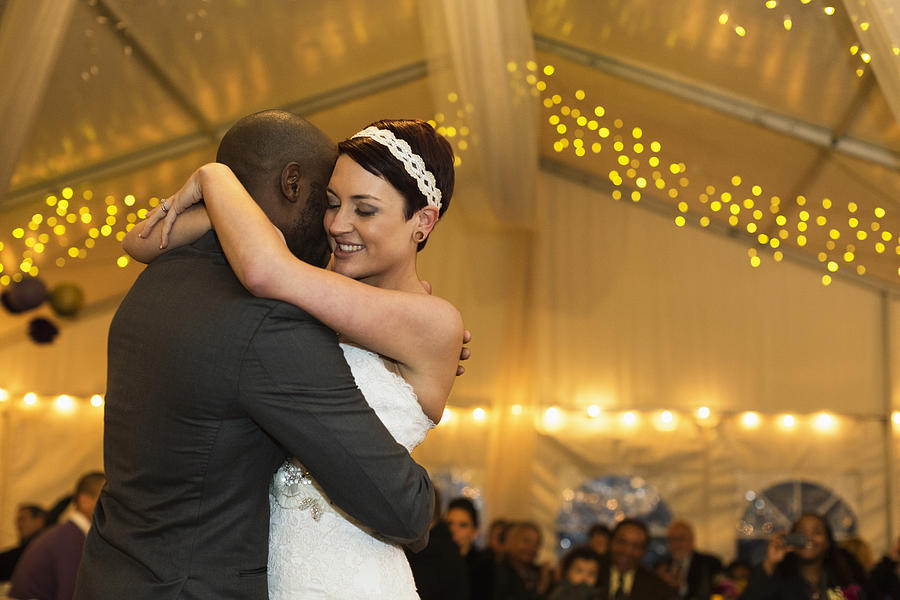 Newlywed couple dancing at reception Photograph by Roberto Westbrook