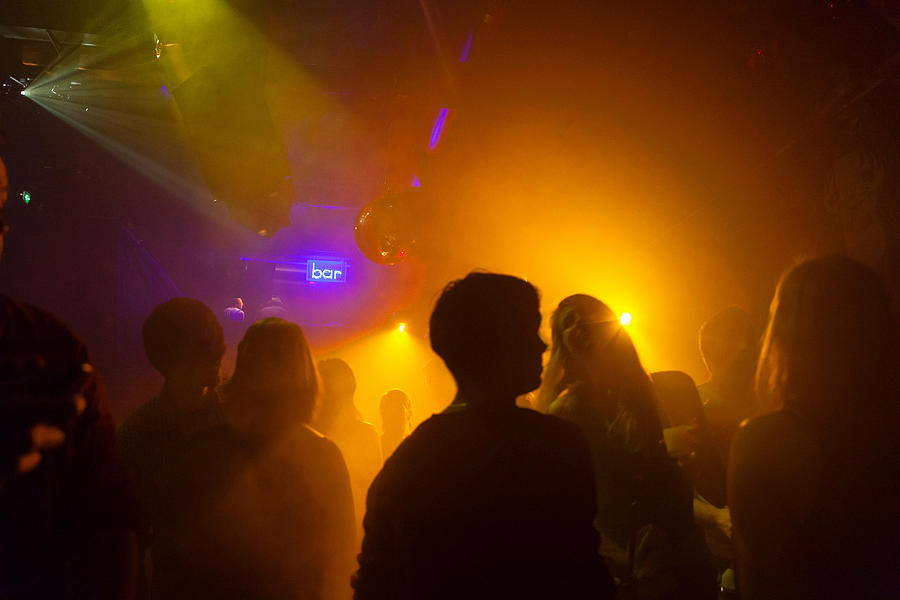 Nightclub scene with people dancing, disco ball, lighting equipment Photograph by Henglein and Steets