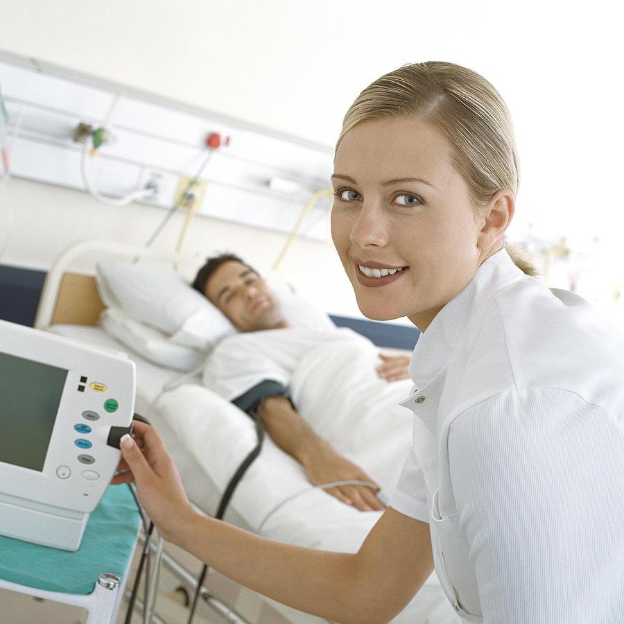 Nurse checking patients monitor Photograph by Vincent Hazat