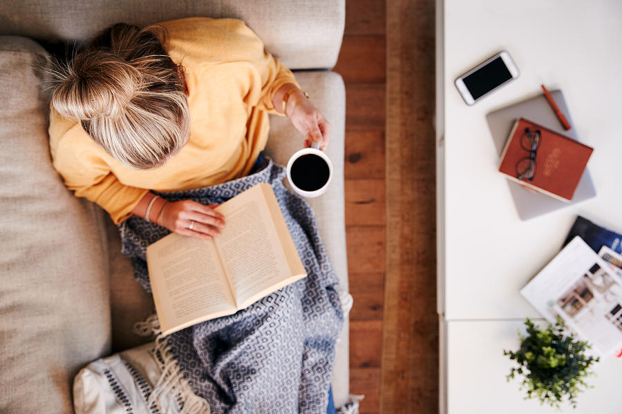 Overhead Shot Looking Down On Woman At Home Lying On Reading Book And Drinking Coffee Photograph by Monkeybusinessimages