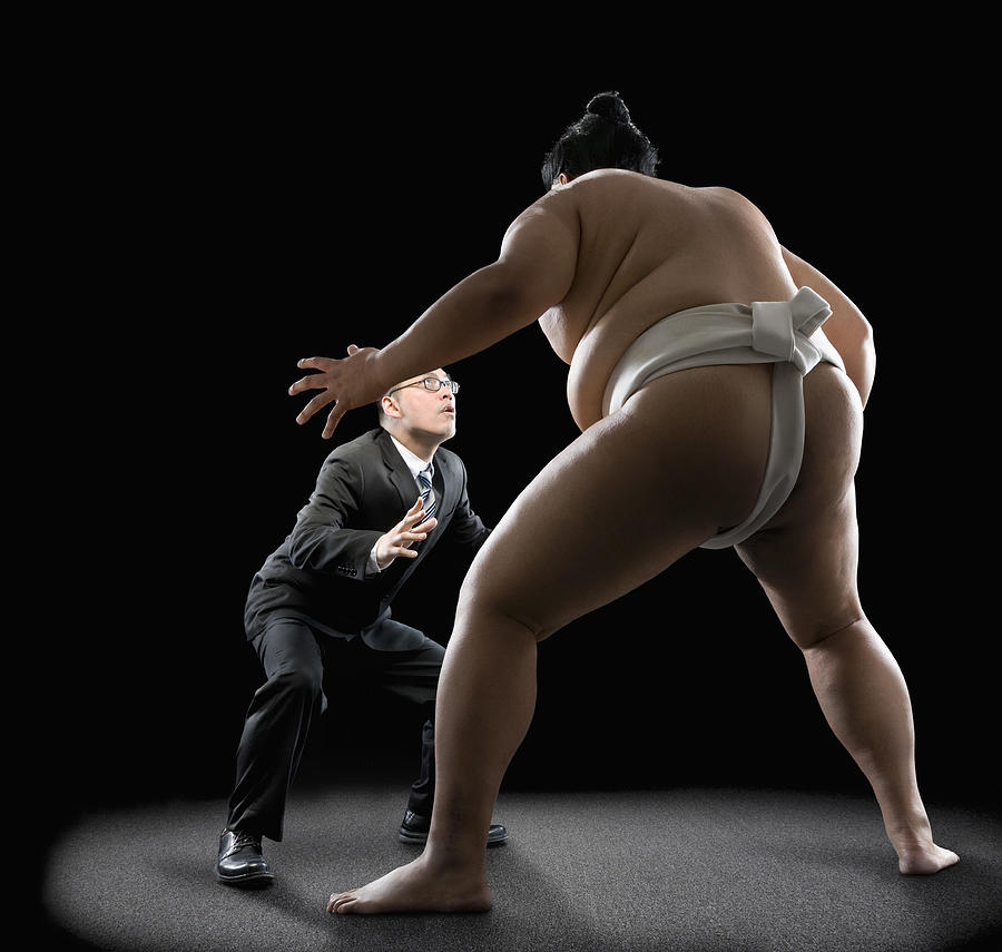 Pacific Islander sumo wrestler challenging businessman Photograph by John M Lund Photography Inc