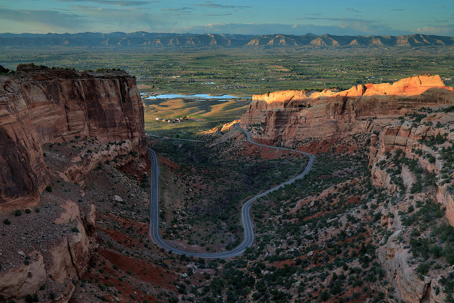 Panoramic view into a valley with a winding road at sunset Photograph by Rainer Grosskopf