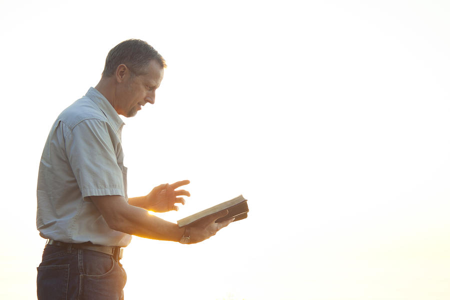 Pastor casually dressed walking in sunlight reading Bible Photograph by Juanestey