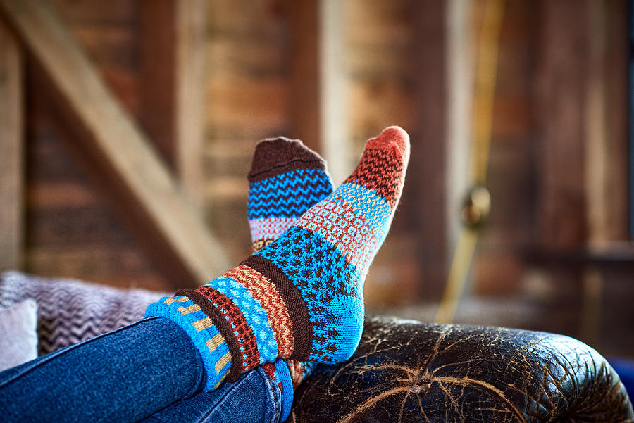 Person wearing patterned socks with feet up on leather sofa Photograph by 10000 Hours