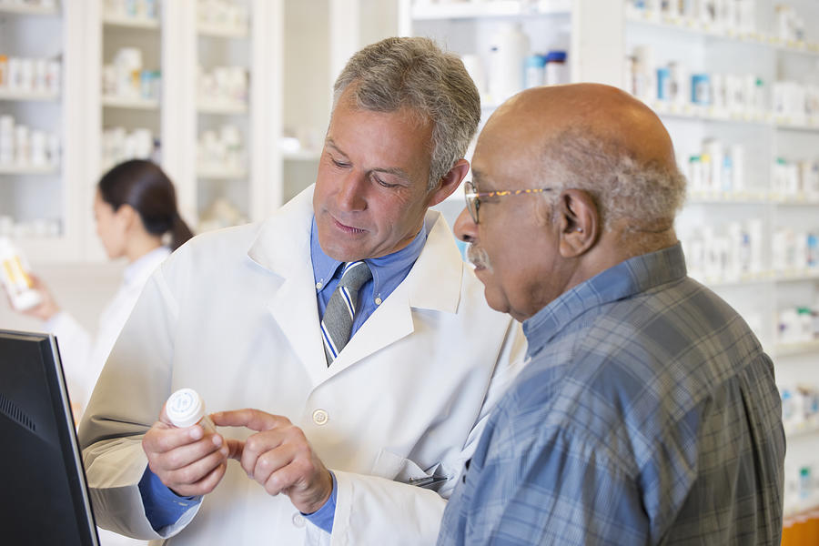 Pharmacist talking to customer about prescription Photograph by Ariel Skelley