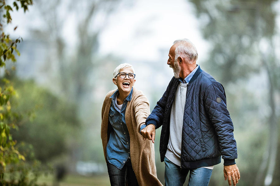 Playful senior couple having fun in the park. Photograph by Skynesher
