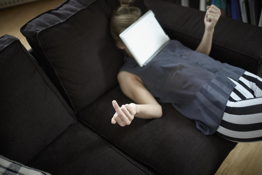 Playful young woman on couch with digital tablet Photograph by Oliver Rossi