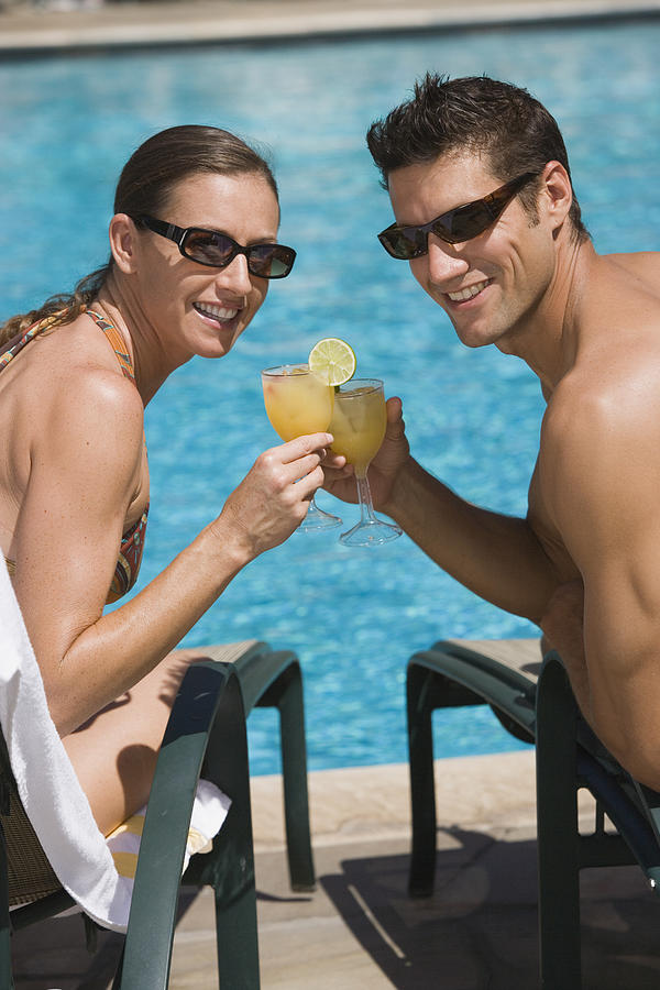 Poolside couple with cocktails Photograph by Comstock Images