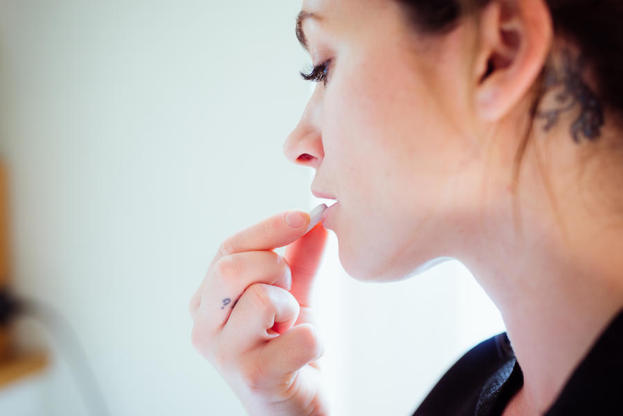 Portrait of a woman taking a pill. Photograph by Guido Mieth