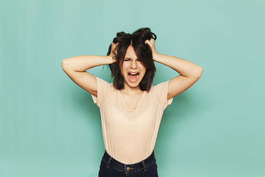 Portrait of frustrated girl shouting with hands in hair against turquoise background Photograph by Paula Winkler