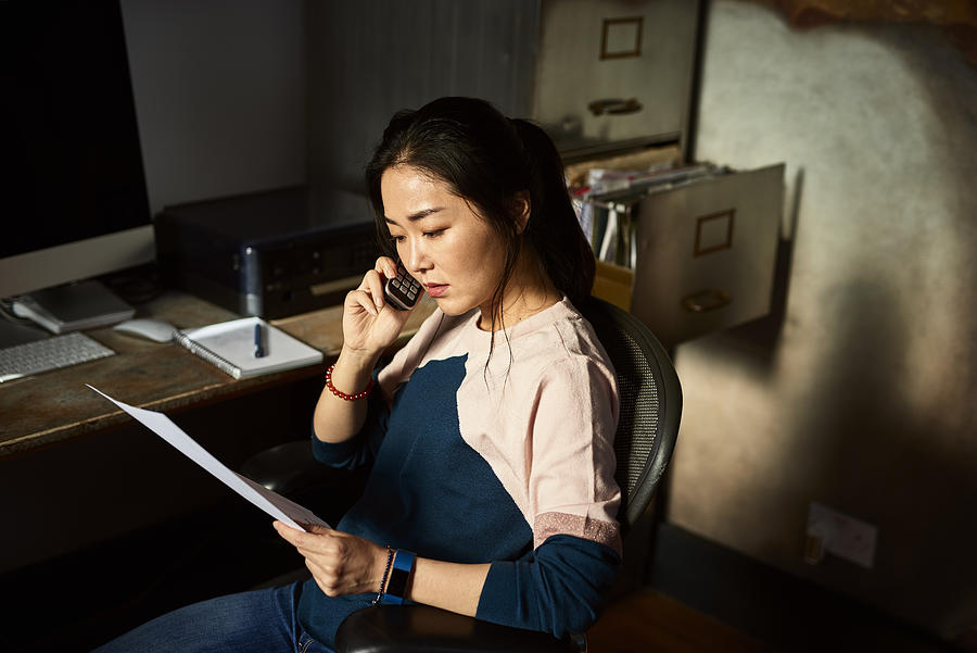Portrait of Korean woman on cell phone reading important document Photograph by 10000 Hours