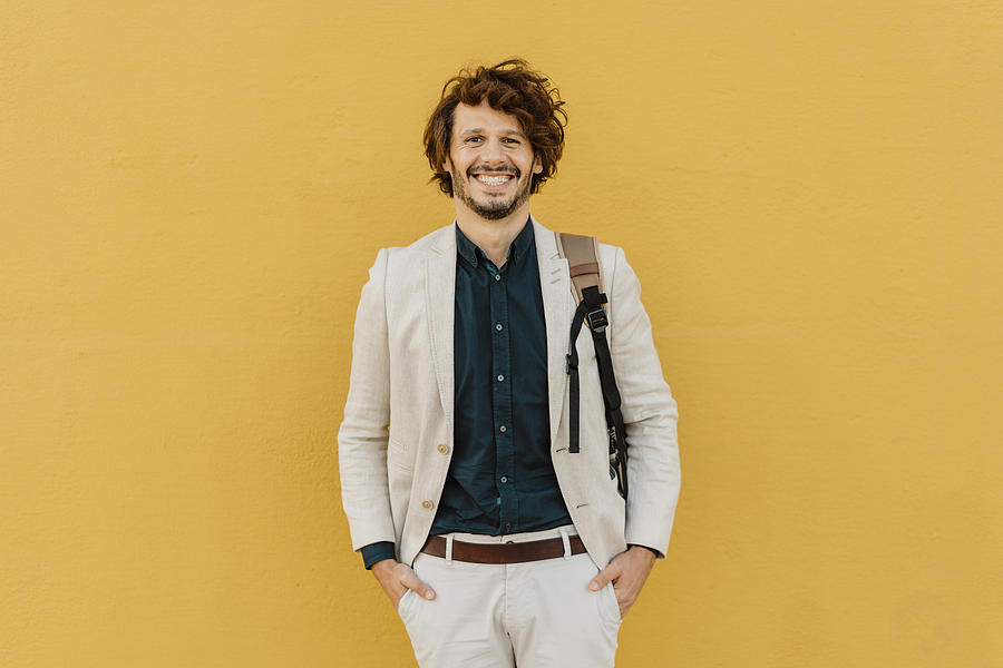 Portrait of laughing businessman with backpack standing in front of yellow wall Photograph by Westend61