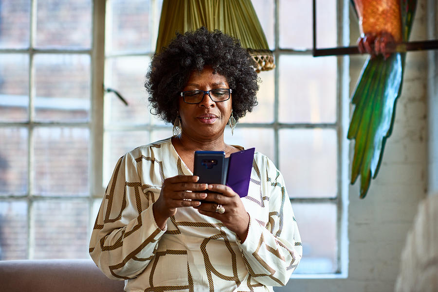 Portrait of mature woman using smartphone at home Photograph by 10000 Hours