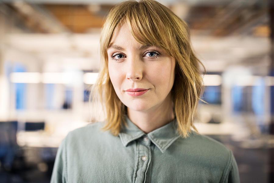 Portrait of young businesswoman in office Photograph by Luis Alvarez