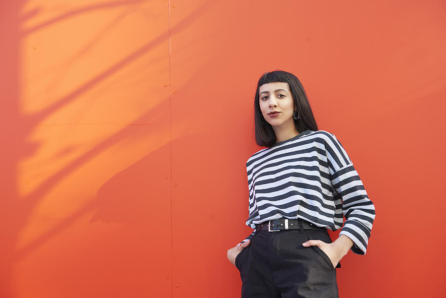 Portrait of young woman standing against red background. Photograph by We Are