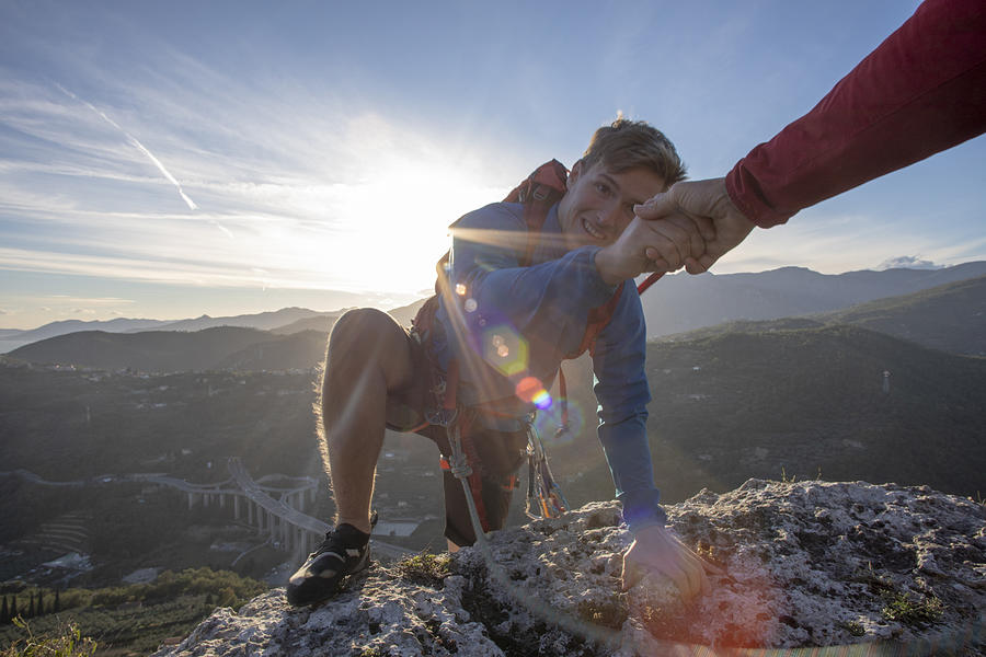 POV down arm to young man climbing up a rock face Photograph by AscentXmedia