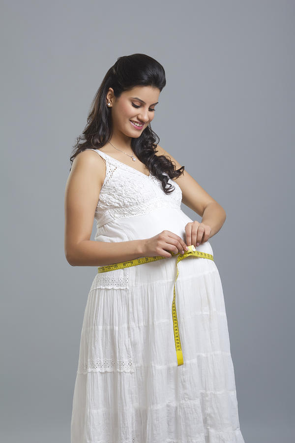Pregnant woman measuring her stomach Photograph by Sudipta Halder