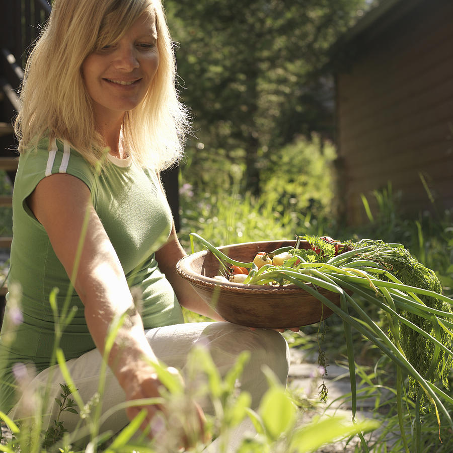 Pregnant woman with herbs and vegetables in baskets, smiling Photograph by Ascent/PKS Media Inc.