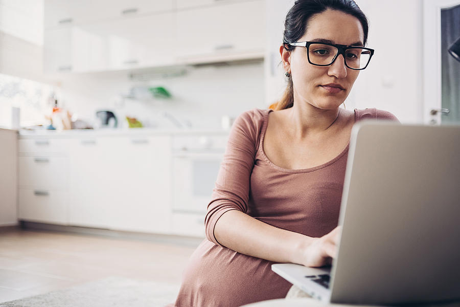 Pregnant young woman with a laptop in the kitchen Photograph by Pixelfit