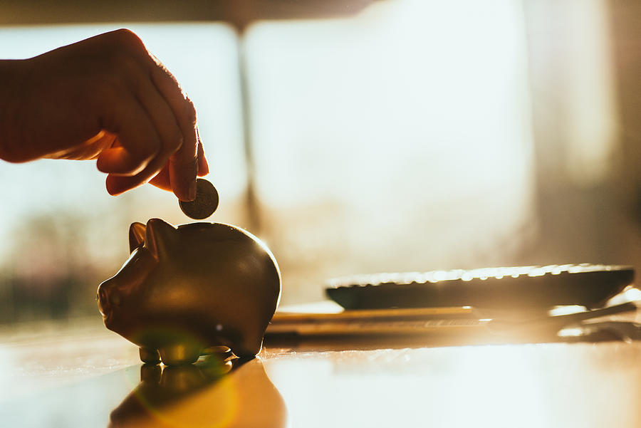 Putting a coin in a gold colored piggy bank at home. Photograph by Guido Mieth