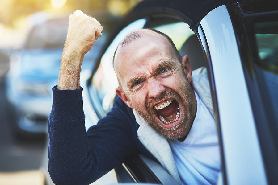 Road rage: out-of-control male driver shaking fist and yelling Photograph by RapidEye