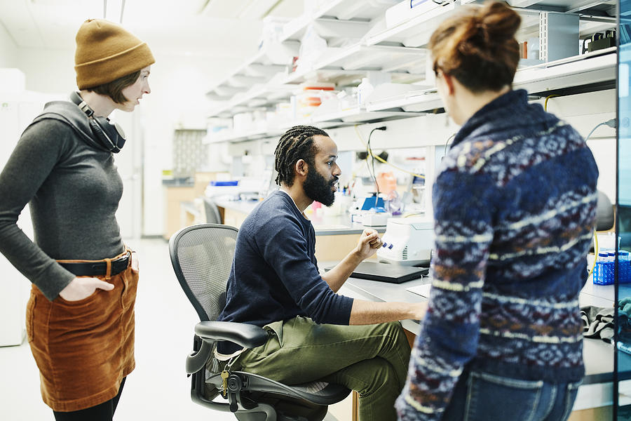 Scientist discussing data with colleagues while working in research lab Photograph by Thomas Barwick