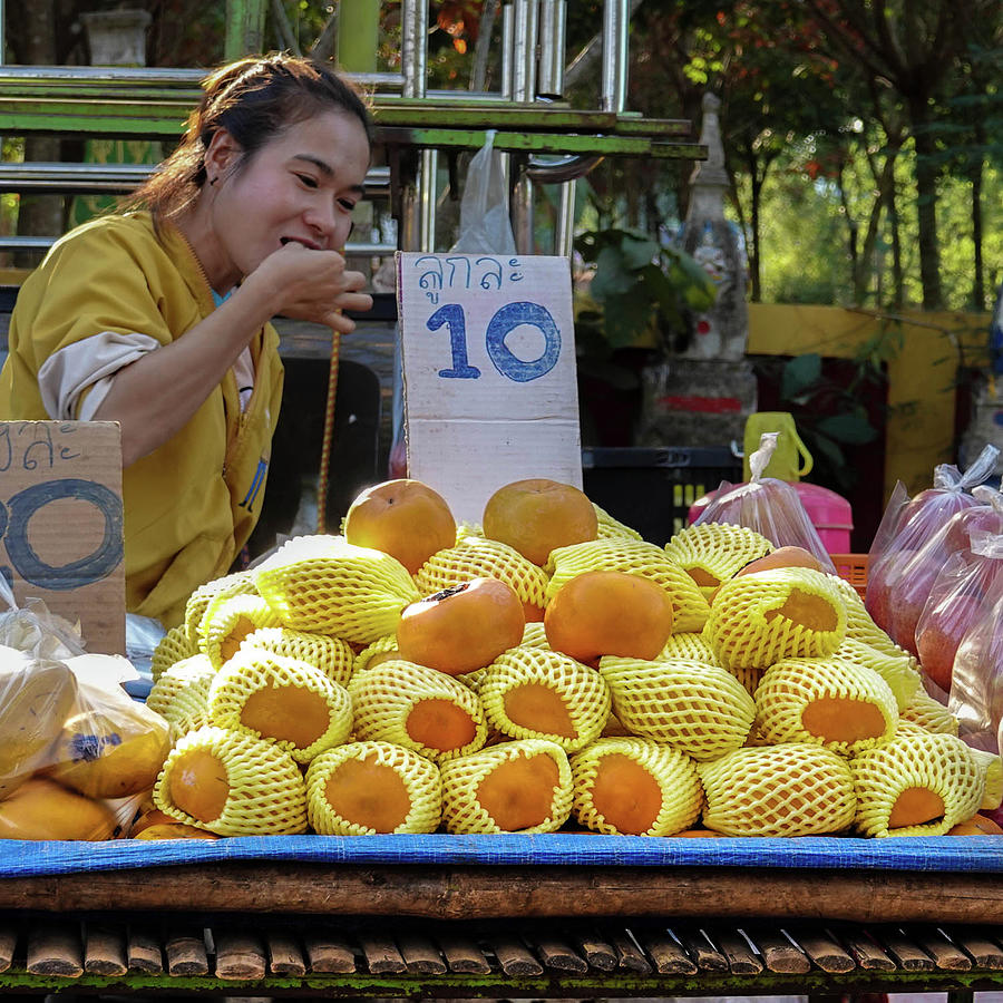 Scrumptious - girl eating fruit at the market by Jeremy Holton