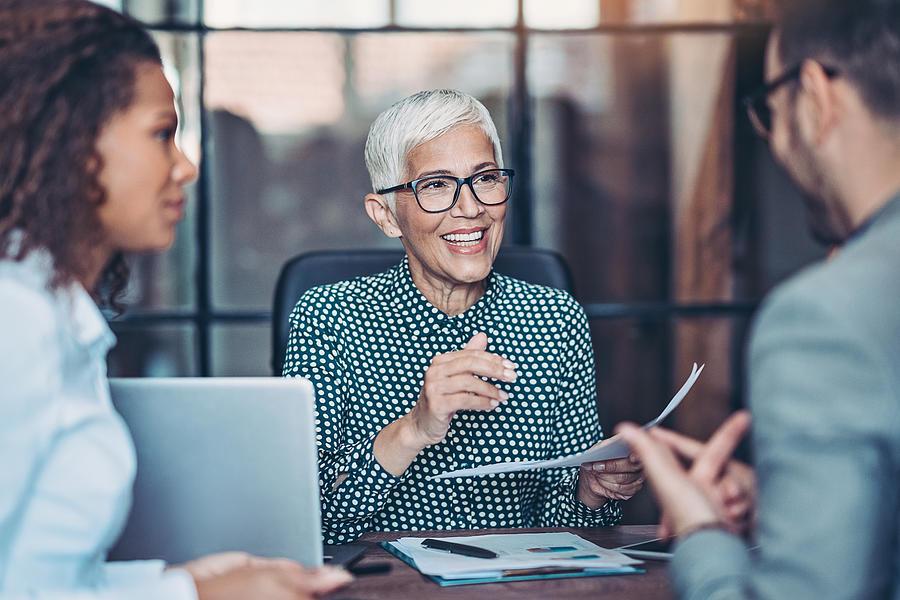 Senior businesswoman talking to her team Photograph by Pixelfit