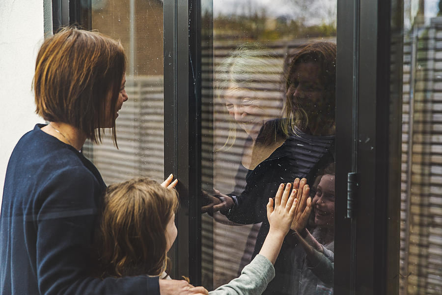 Senior lady speaking to daughter and granddaughter through window Photograph by Justin Paget