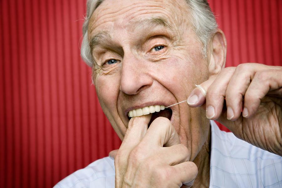 Senior man using dental floss to clean teeth, close-up Photograph by David Sacks