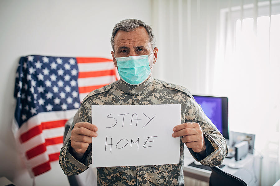 Senior military soldier holding paper with message stay home Photograph by Hirurg