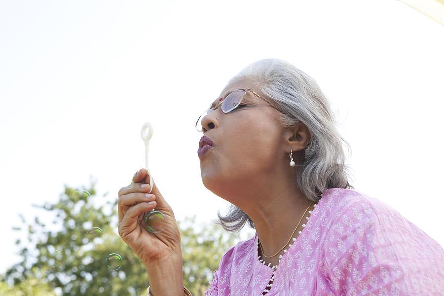 Senior woman blowing bubbles Photograph by Ravi Ranjan