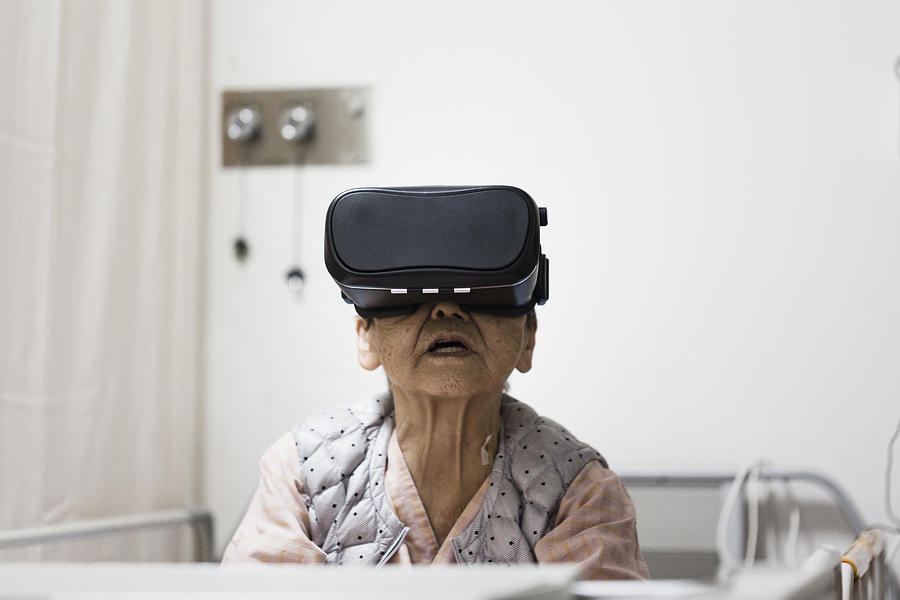 Senior woman in the hospital wearing a Virtual Reality headset Photograph by Kohei Hara