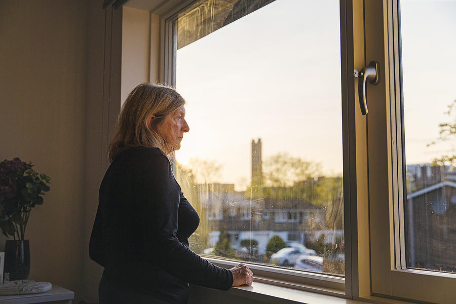 Senior woman looking out of her bedroom window at sunset Photograph by Justin Paget