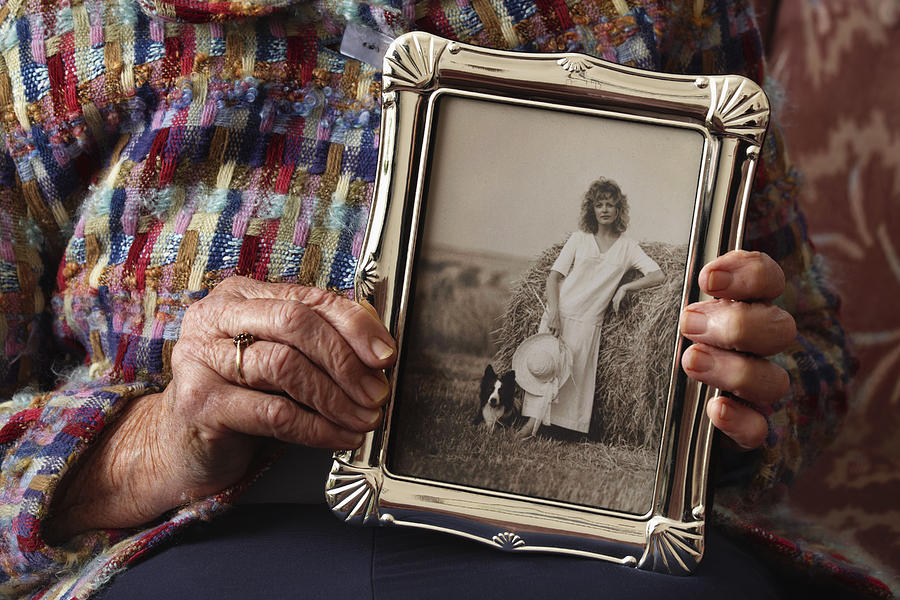 Seniors hands holding vintage photo of herself Photograph by Andrew Bret Wallis