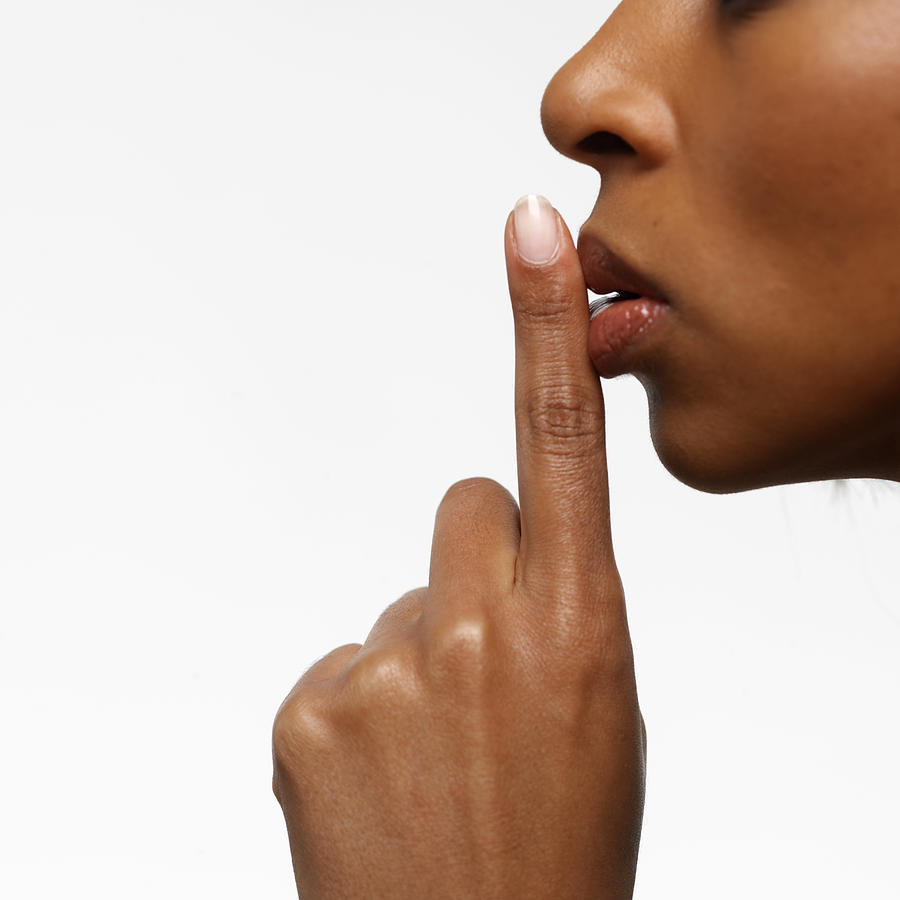 Side profile of a young businesswoman with her finger on her lips Photograph by George Doyle