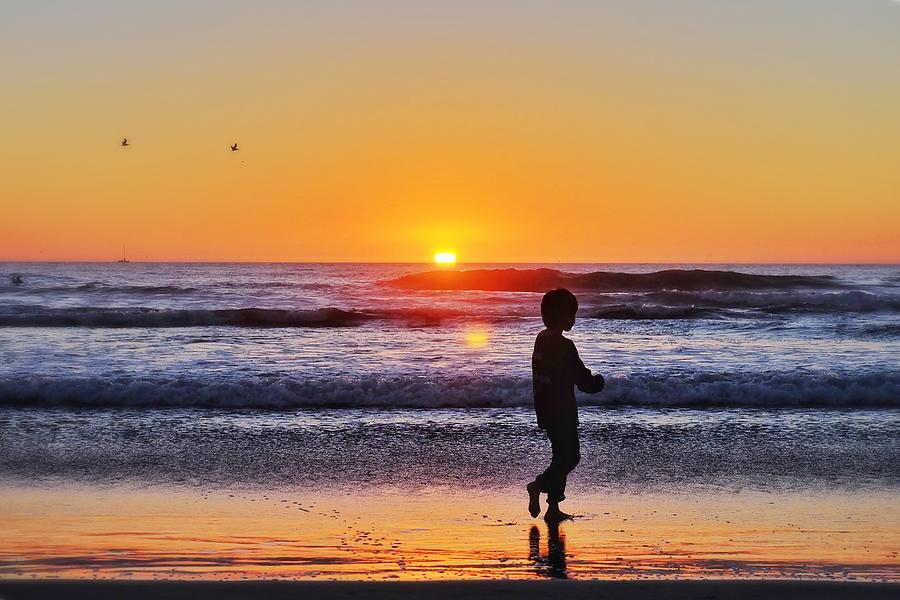 Silhouette Boy Walking At Beach Against Sky During Sunset Photograph by Jesse Coleman / EyeEm
