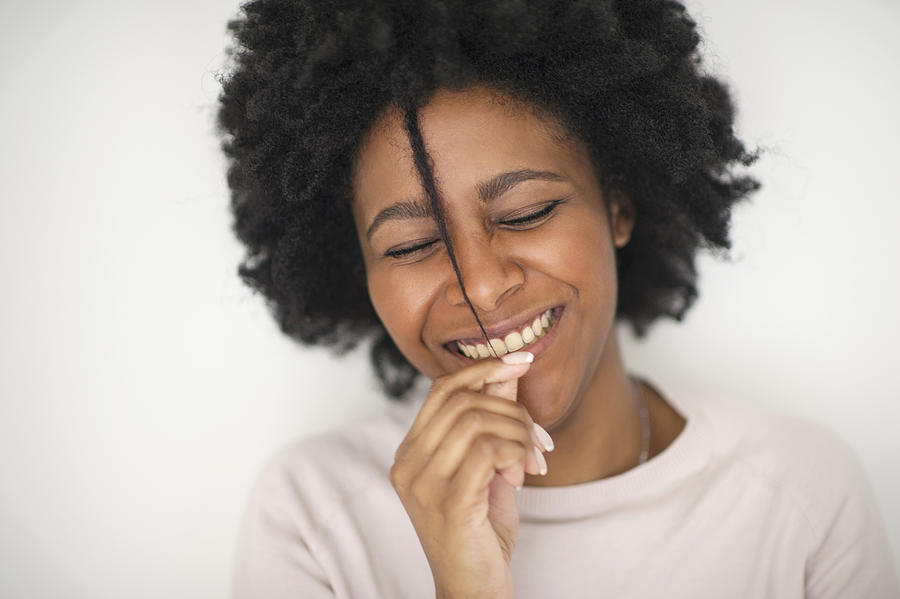 Smiling Black woman playing with hair Photograph by Shestock