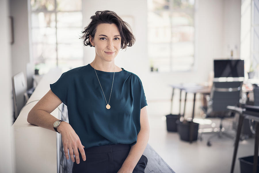 Smiling businesswoman in creative office Photograph by Portra