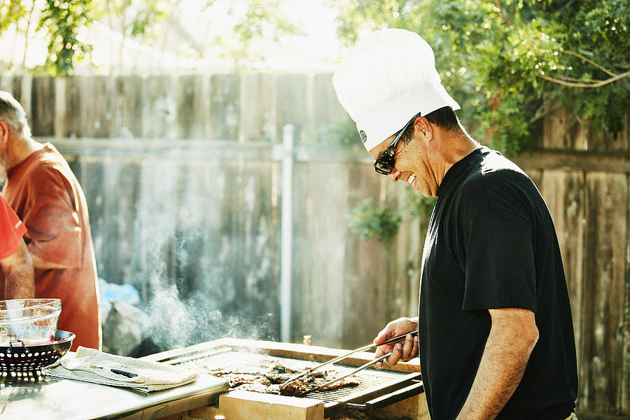 Smiling father grilling in backyard during family barbecue Photograph by Thomas Barwick
