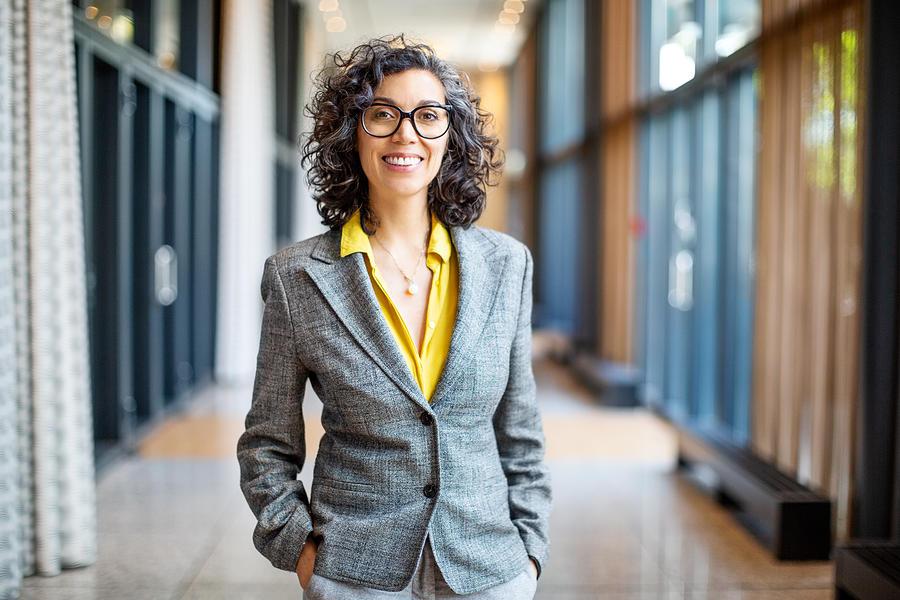 Smiling female entrepreneur outside auditorium Photograph by Luis Alvarez