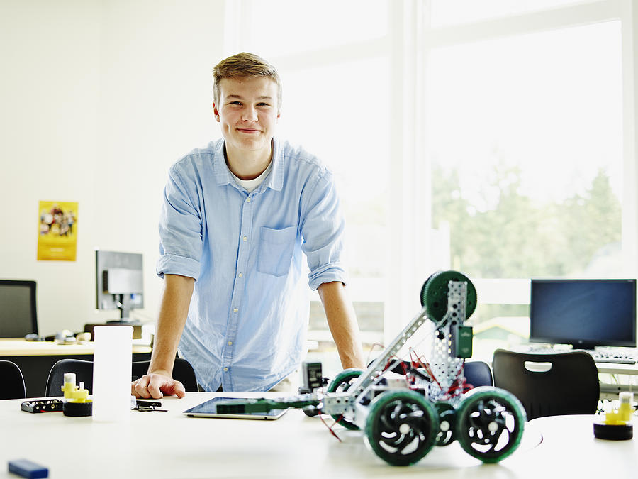 Smiling male student in classroom with robot Photograph by Thomas Barwick